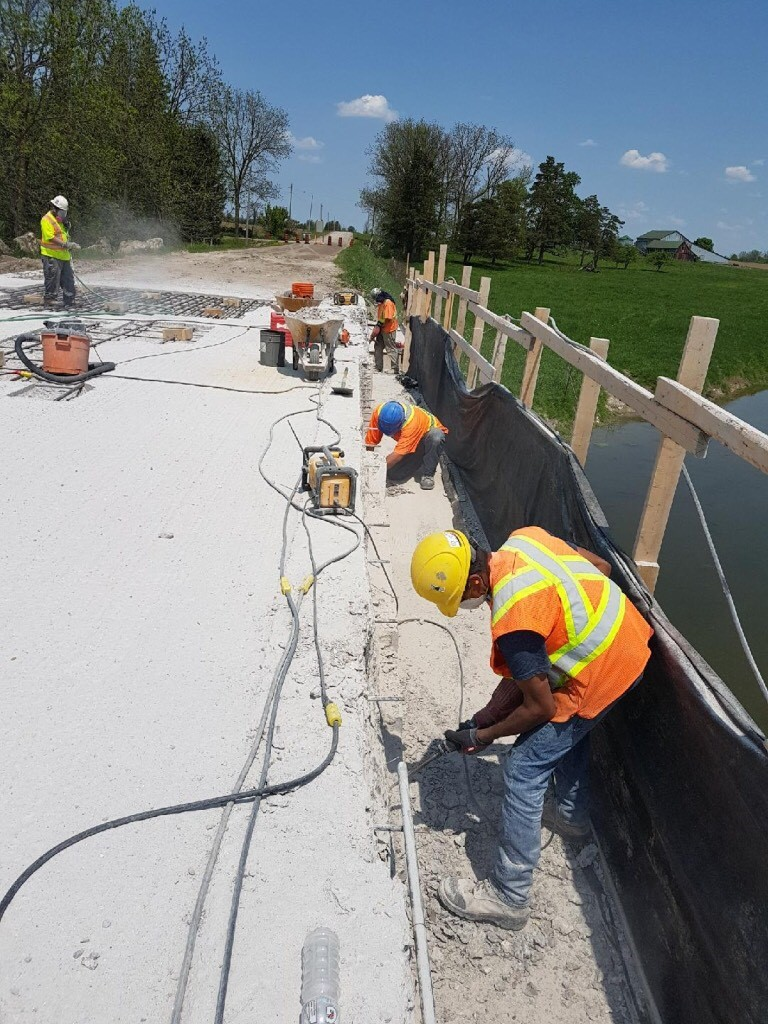 Chipping away bad concrete on a bridge deck in MItchell
